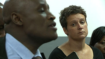 Charlotte Campbell casts a grim look at Mr. Ondeiki, the attorney for the accused in her rape case.